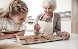Grand-mère heureuse serrant la crème sur des biscuits de vacances Images stock