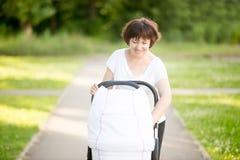 Grand-mère marchant avec une poussette de bébé en parc Photos stock