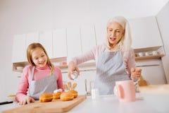 Grand-mère mignonne et petite-fille heureuses appréciant la cuisson Photos libres de droits