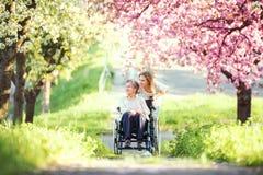 Grand-mère pluse âgé dans le fauteuil roulant avec la nature de petite-fille au printemps Photos stock