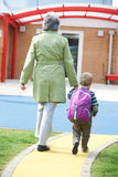 Grand-mère portant le petit-fils à l'école photos stock