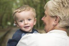 Grand-mère portant son petit-fils heureux de deux ans Images stock