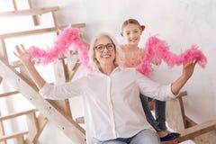 Grand-mère positive et petite-fille joyeuses tenant un boa de plume Photos stock