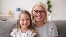 Grand-mère principale et petite-fille tirées de portrait faisant l'appel visuel banque de vidéos