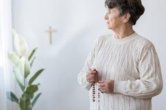 Grand-mère religieuse priant dans l'église Photographie stock libre de droits