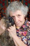 Grand-mère s'asseyant avec le chat sur ses mains Photographie stock libre de droits