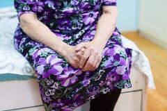 Grand-mère s'asseyant sur le lit Photographie stock libre de droits