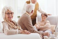 Grand-mère s'asseyant sur un divan Photo stock
