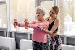 Grand-mère sereine faisant des exercices avec l'haltère Photographie stock libre de droits