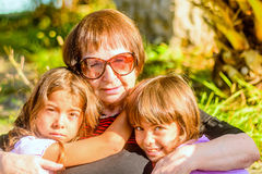 Grand-mère tenant ses deux petite-filles image stock