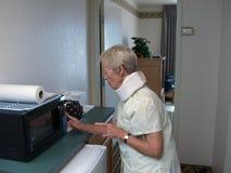 Grand-mère utilisant une micro-onde photo stock