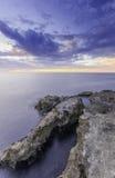 Grand majestic rocks on the shore silky ocean Stock Photos