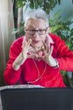 Grand-maman à l'aide de l'ordinateur portable, de l'appareil-photo et des écouteurs pour les connexions éloignées Photo stock
