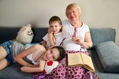 Grand-maman avec se reposer de sourire de petits-enfants sur le divan Photographie stock