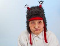 Grand-maman dans le chapeau drôle avec une expression boudeuse Image stock