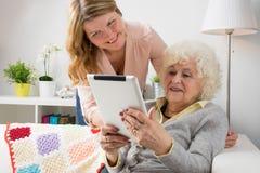 Grand-maman de enseignement de petite-fille comment utiliser la tablette Images stock