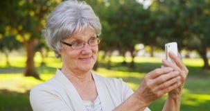 Grand-maman de hanche prenant des selfies au parc images stock