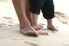 Grand-maman et la peu à un pieds dans le sable Photos libres de droits