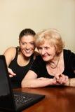 Grand-maman et petite-fille avec un ordinateur portatif Photos libres de droits
