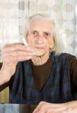 Grand-maman fumant une cigarette à la maison Images stock