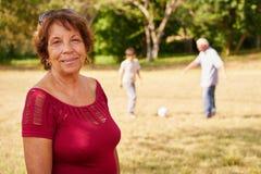 Grand-maman supérieure heureuse jouant le football avec la famille Photographie stock libre de droits