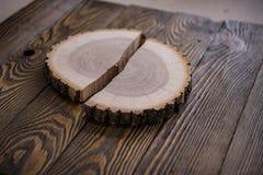 Grand morceau circulaire de section transversale en bois avec le modèle et les fissures de texture d'anneau sur un fond en bois image libre de droits