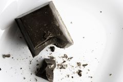 Grand morceau coupé de mensonges de chocolat d'un plat en céramique blanc images libres de droits