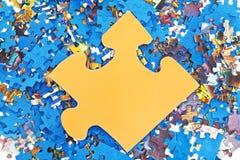 Grand morceau jaune sur la pile des puzzles démontés Photographie stock libre de droits