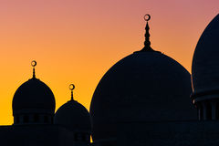 Grand Mosque Domes Silhouette. Three domes of a grand mosque with crescent spires are silhouetted against the setting sun Royalty Free Stock Image