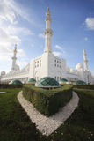 Grand mosque outside. Vertical shot looking at the spires of the Grand Mosque in Abu Dhabi. Three towers balance the picture with green grass in foreground and Stock Photo