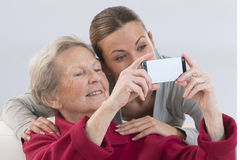 Grand-Mother and attractive young grand-daughter photographing Stock Photos
