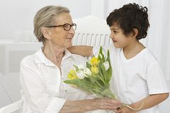 Grand mother receiving flowers from her grandson Royalty Free Stock Photography