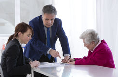 Grand mother signing insurance contract and donation to her gran Stock Photo