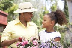 Grand-mère avec la petite-fille faisant du jardinage ensemble Images stock