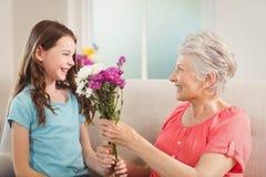 Grand-mère donnant un groupe de fleurs à sa petite-fille Photo libre de droits