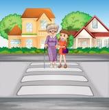 Grand-mère et enfant traversant la route Photographie stock