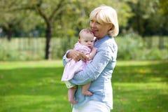 Grand-mère tenant la petite-fille de bébé Photographie stock libre de droits
