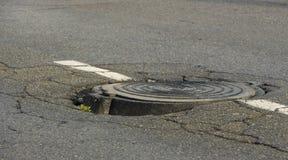 Grand nid de poule dans l'asphalte et la couverture de trou d'homme circulaire des eaux d'égout bien dans la route, Images libres de droits