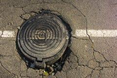 Grand nid de poule dans l'asphalte et la couverture de trou d'homme circulaire des eaux d'égout bien dans la route, Photo libre de droits