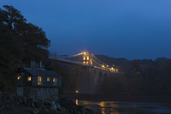 Grand night-time view of the historic Menai Suspension Bridge, Anglesey, North Wales. Grand view of the Menai Suspension Bridge illuminated at night-time Stock Photos