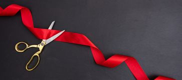 Grand opening. Top view of gold scissors cutting red silk ribbon against black background, banner,. Copy space stock photo