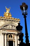 Grand Opera Paris Garnier golden statue and facade front view in front of old Lampposts france. Golden statue on the rooftop and front view with details of the stock photo
