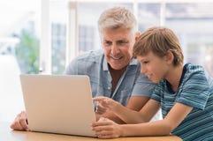 Grand-père à l'aide de l'ordinateur portable avec le petit-fils Photo libre de droits