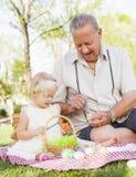 Grand-père affectueux et petite-fille colorant des oeufs de pâques sur la couverture à Photographie stock libre de droits