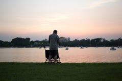 Grand-père avec des petits-enfants dans la poussette se tenant prêt le lac Photos stock