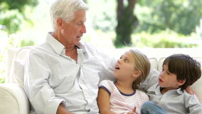 Grand-père avec des petits-enfants s'asseyant sur Sofa At Home banque de vidéos