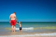 Grand-père avec le petit-fils sur la plage photographie stock