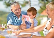 Grand-père de sourire jouant des cartes avec le petit-fils Photographie stock