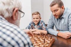 Grand-père entreprenant une démarche dans le jeu d'échecs tandis que le petit-fils et le fils sont photographie stock libre de droits