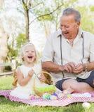 Grand-père espiègle et petite-fille colorant des oeufs de pâques sur la couverture à Photo stock